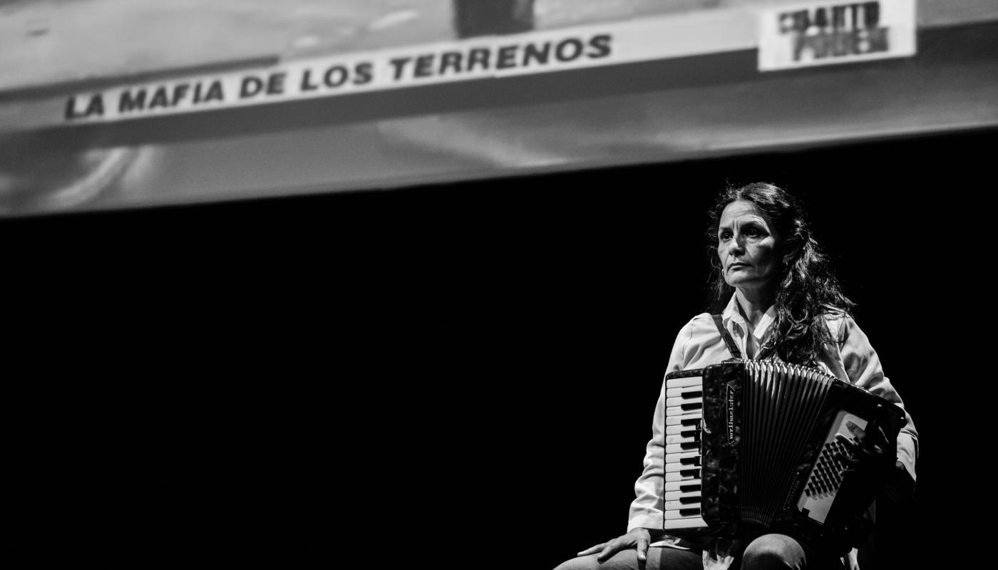 Black and white photo of a woman holding an accordion, sitting on stage in front of a projected image