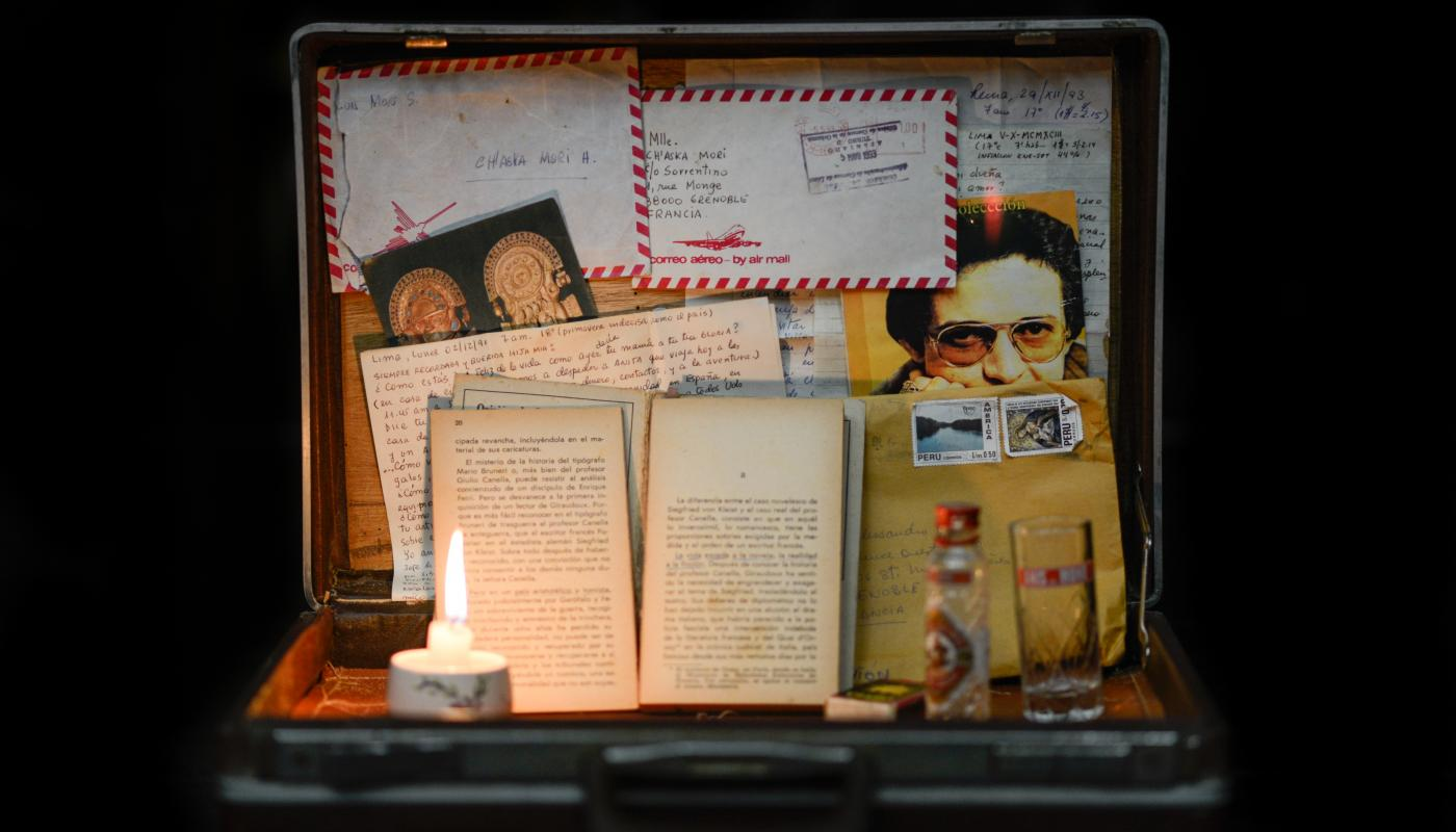 An open suitcase holding various papers and a lit candle