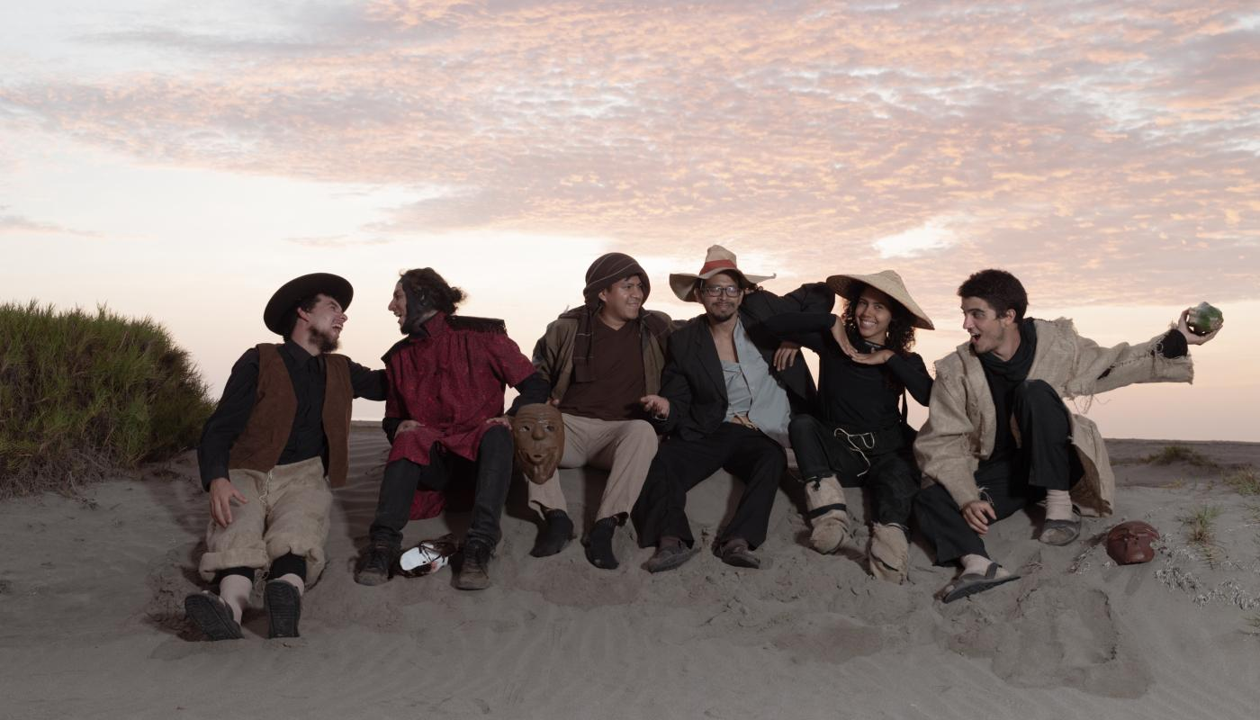 Group of musicians, sitting on a sand dune in front of a sunset