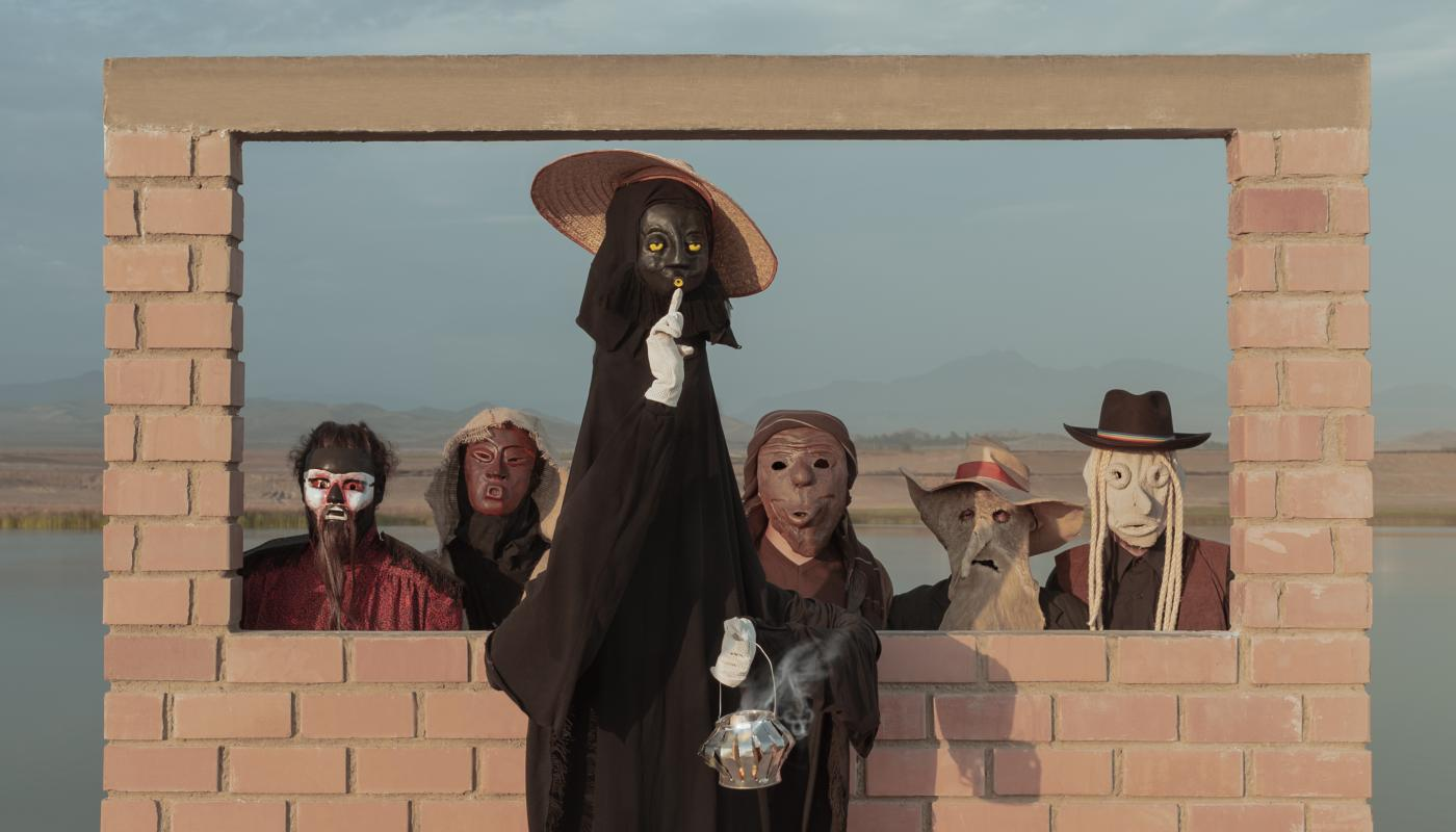 5 people wearing masks in front of a brick structure