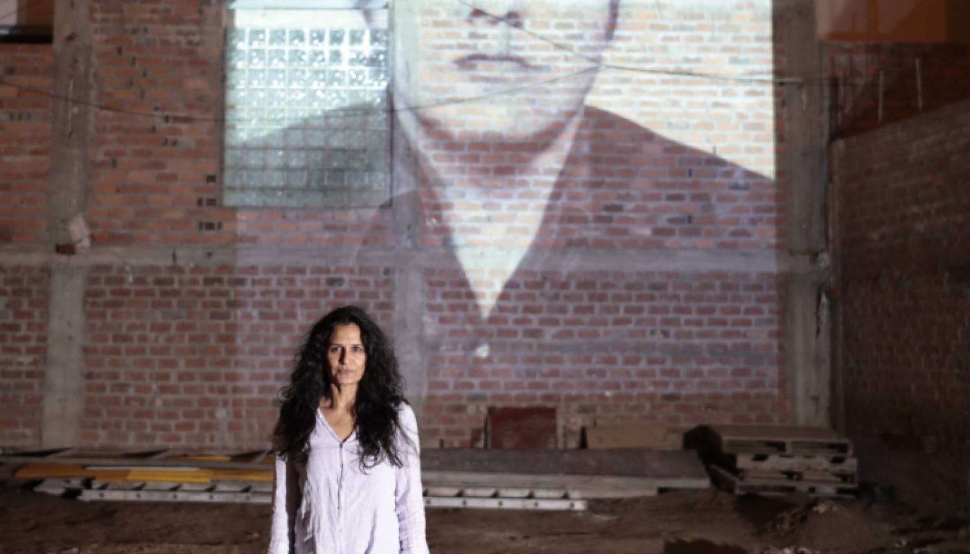 Woman standing in front of a brick wall, with an image of a man projected onto it