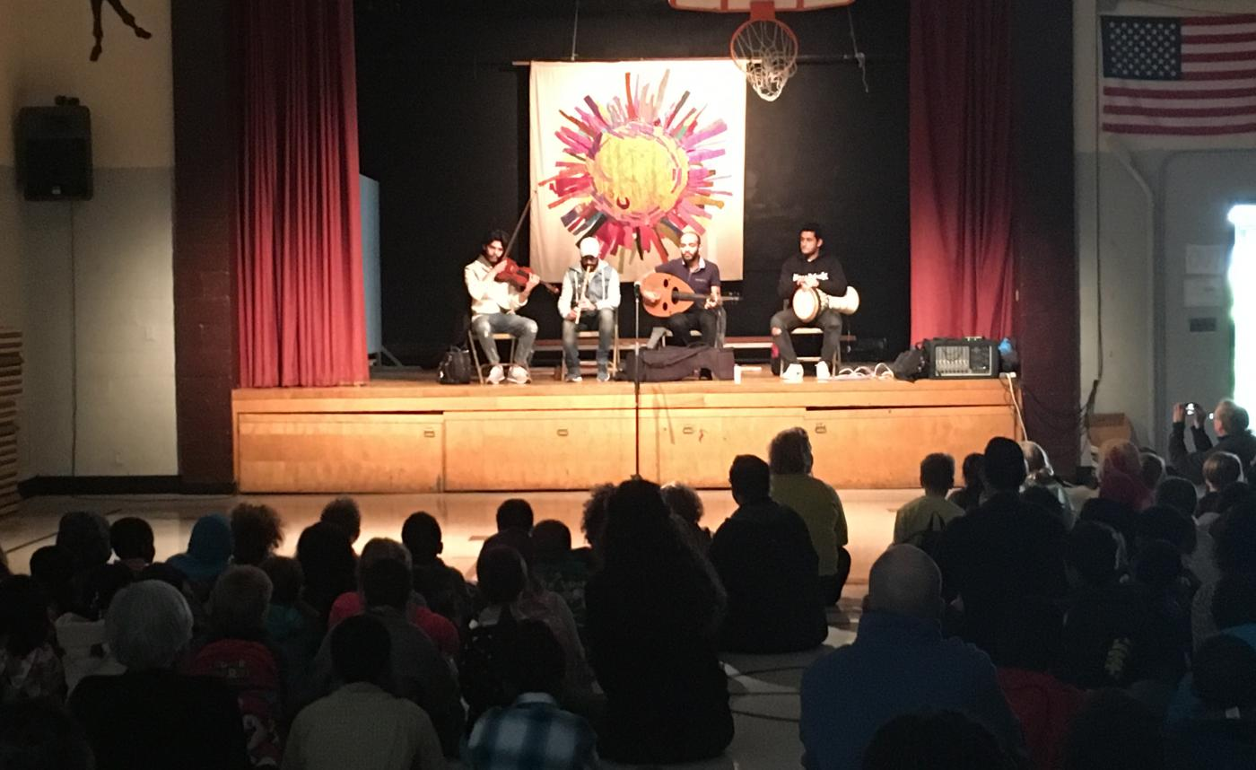 A 4 piece band plays classical Egyptian instruments on a stage in a school theater/gymnasium. An audience of students fill the foreground
