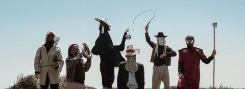 6 people wearing masks on a hill in front of blue sky