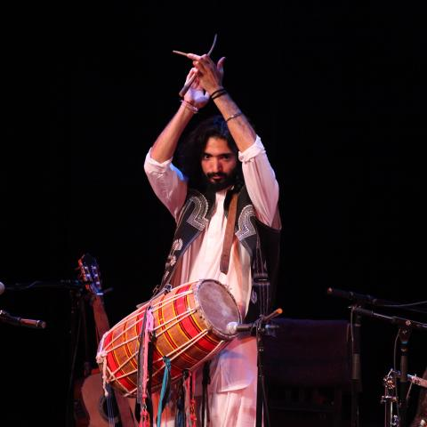 Man on stage with a traditional drum, hands in the air clapping