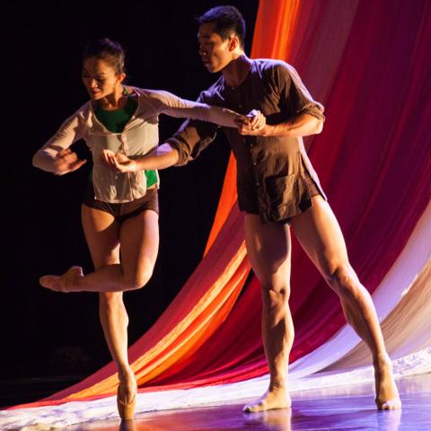 Two dancers on stage in front of flowing red fabric