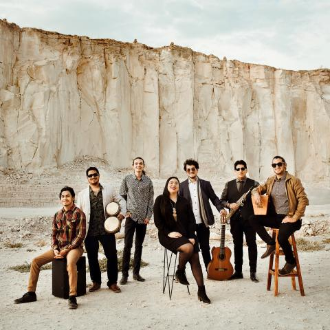 Seven people standing together with various instruments in front of a large white cliff